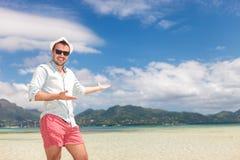 Den lyckliga mannen välkomnar dig till den soliga stranden Arkivbilder