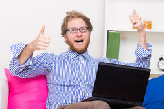 Den lyckliga mannen visar det reko tecknet framme av en dator Arkivfoton