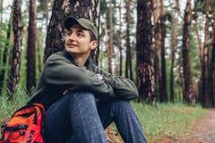 Den lyckliga manturisten som vilar i vårskoghandelsresande, stoppade för att koppla av Campa, resande- och sportbegrepp arkivbilder
