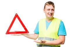 Den lyckliga mekanikern visar tecknet för det nöd- stoppet på vit Royaltyfri Foto