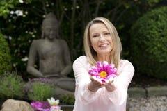 Den lyckliga mellersta åldriga kvinnan erbjuder blommor i zenträdgård royaltyfri foto