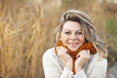 Den lyckliga mitt åldrades kvinnan med sweatern och halsduken arkivbild
