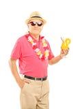 Den lyckliga mitt åldrades mannen på en semester som rymmer en coctail Royaltyfria Foton