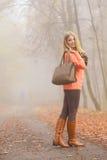 Den lyckliga modekvinnan med handväskan i höst parkerar Arkivbild