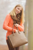 Den lyckliga modekvinnan med handväskan i höst parkerar Royaltyfri Foto