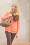 Den lyckliga modekvinnan med handväskan i höst parkerar Arkivfoton