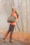 Den lyckliga modekvinnan med handväskan i höst parkerar Fotografering för Bildbyråer