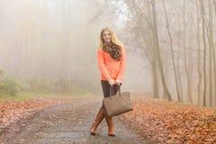 Den lyckliga modekvinnan med handväskan i höst parkerar Royaltyfri Fotografi