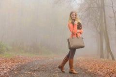 Den lyckliga modekvinnan med handväskan i höst parkerar Royaltyfri Bild