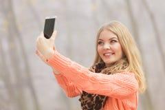 Den lyckliga modekvinnan parkerar in att ta selfiefotoet Arkivfoton