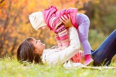 Den lyckliga moder- och ungeflickan spelar utomhus i nedgång Arkivbilder