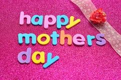 Den lyckliga moderdagen på en rosa bakgrund med ett rosa band och ett konstgjort steg Arkivfoto