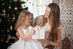 Den lyckliga modern i det vita omslaget ger gåvan till en dotter på jul Arkivbilder