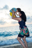 Den lyckliga modern kastar upp sonen på stranden Arkivfoto