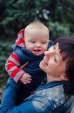 Den lyckliga modern kramar henne som ler, behandla som ett barn Arkivfoto