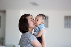 Den lyckliga modern kysser henne behandla som ett barn Arkivfoto