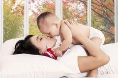 Den lyckliga modern kysser hennes behandla som ett barn flickan Arkivfoto