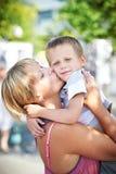 Den lyckliga modern kysser hennes son Royaltyfri Fotografi