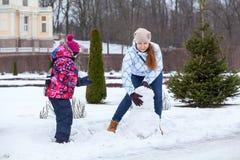 Den lyckliga modern med barndanandesnögubben med insnöad vinter parkerar Arkivbild