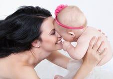 Den lyckliga modern med behandla som ett barn över white Fotografering för Bildbyråer