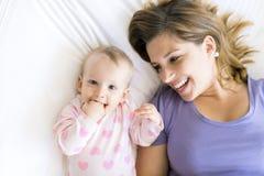 Den lyckliga modern med behandla som ett barn att ligga på säng hemma arkivbilder