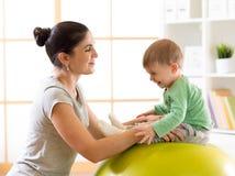 Den lyckliga modern med behandla som ett barn göra gymnastik på den stora konditionbollen i idrottshallen Fotografering för Bildbyråer