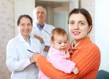 Den lyckliga modern med behandla som ett barn i armar mot doktorer Royaltyfri Foto