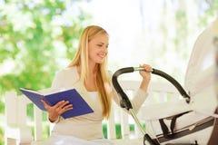 Den lyckliga modern med boken och sittvagnen parkerar in Royaltyfri Fotografi