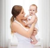 Den lyckliga modern med förtjusande behandla som ett barn Arkivfoto