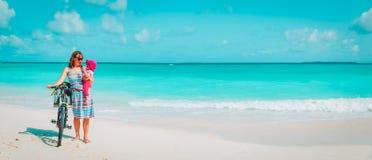 Den lyckliga modern med gulligt litet behandla som ett barn flickacykeln p? stranden royaltyfria foton