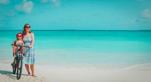 Den lyckliga modern med gulligt litet behandla som ett barn flickacykeln p? stranden royaltyfri fotografi