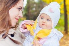 Den lyckliga modern med henne behandla som ett barn på utomhus-, höst parkerar Royaltyfri Foto