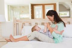 Den lyckliga modern med henne behandla som ett barn pojken Royaltyfri Foto