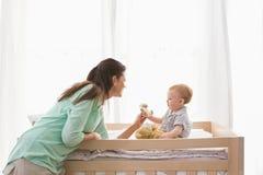 Den lyckliga modern med henne behandla som ett barn pojken Arkivfoto