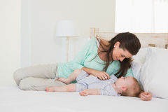 Den lyckliga modern med henne behandla som ett barn pojken Arkivbilder
