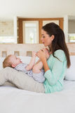 Den lyckliga modern med henne behandla som ett barn pojken Royaltyfri Bild