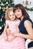 Den lyckliga modern med hennes dotter sitter nära en vit spis bredvid ett träd som dekoreras med leksaker royaltyfri foto