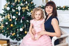 Den lyckliga modern med hennes dotter sitter nära en vit spis bredvid ett träd som dekoreras med leksaker arkivbild