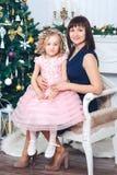 Den lyckliga modern med hennes dotter sitter nära en vit spis bredvid ett träd som dekoreras med leksaker arkivfoton