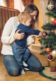Den lyckliga modern med hennes 10 gamla månader behandla som ett barn pojken som dekorerar Christma Arkivbild