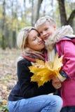 Den lyckliga modern med lönnbroschyrer kramar hennes dotter Royaltyfri Fotografi