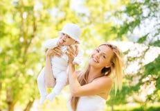 Den lyckliga modern med lite behandla som ett barn parkerar in Arkivbild