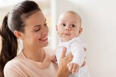Den lyckliga modern med lite behandla som ett barn pojken hemma arkivfoton