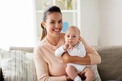 Den lyckliga modern med lite behandla som ett barn pojken hemma royaltyfri fotografi
