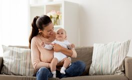 Den lyckliga modern med lite behandla som ett barn pojken hemma royaltyfria foton