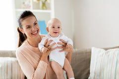 Den lyckliga modern med lite behandla som ett barn pojken hemma royaltyfri foto