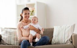 Den lyckliga modern med lite behandla som ett barn pojken hemma fotografering för bildbyråer