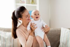 Den lyckliga modern med lite behandla som ett barn pojken hemma royaltyfri bild