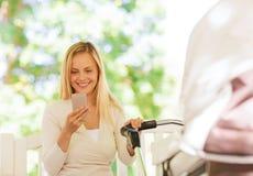 Den lyckliga modern med smartphonen och sittvagnen parkerar in Royaltyfri Fotografi