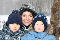 Den lyckliga modern med två söner ler i vinterdag Fotografering för Bildbyråer